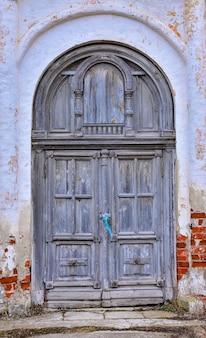 Grijze houten deur in de muur