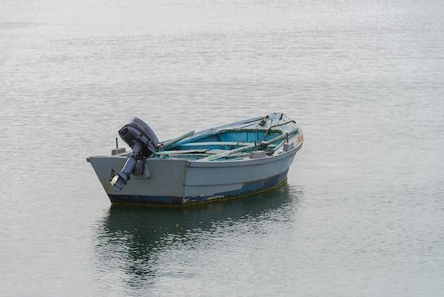 Grijze houten vissersmotorboot afgemeerd aan de kust
