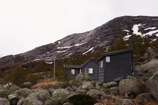 Grijze huizen staan tussen de rotsen in de bergen