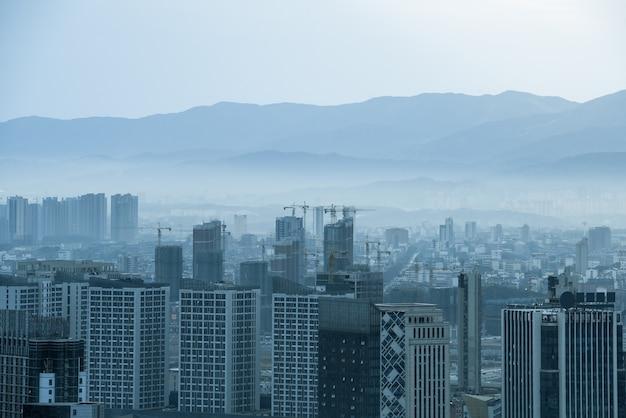 Grijze industriestad, omgeven door bergen in de verte