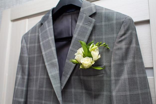 Grijze jas in een kooi met een corsage aan de deur