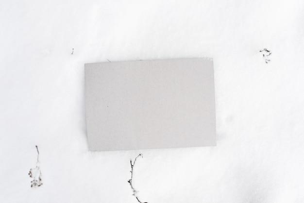 Grijze kartonnen mock-up. blanco vel karton liggend in de sneeuw, bovenaanzicht. lege ruimte voor tekst, branding, bericht.