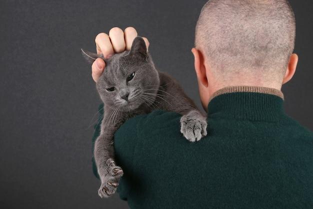 Grijze kat, zittend op de schouder van een man