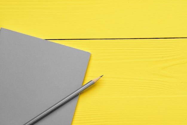 Grijze kladblok met potlood op gele houten bovenaanzicht