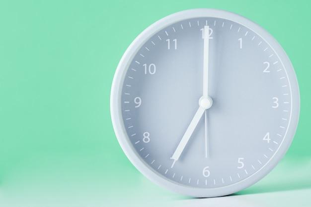 Grijze klassieke wekker op een pastel groen met kopie ruimte