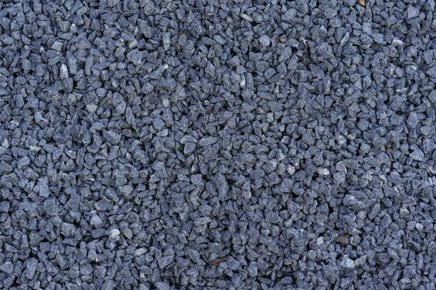 Grijze kleine stenen gemalen textuur. donkergrijze kleine weg stenen achtergrond.