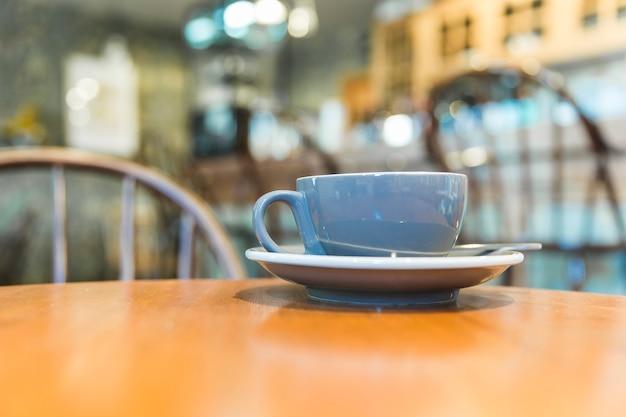 Grijze koffiekop op houten lijst
