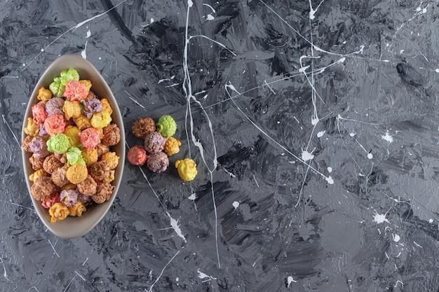 Grijze kom heerlijke kleurrijke popcorns op marmeren achtergrond.