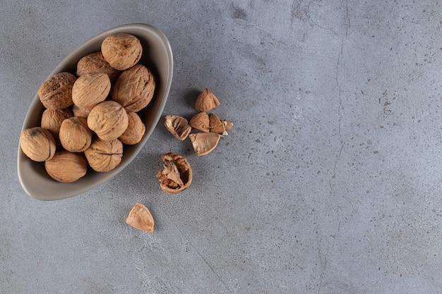 Grijze kom organische gepelde walnoten op steenachtergrond.