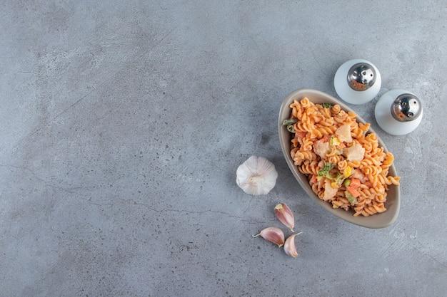 Grijze kom van twee verschillende romige pasta op stenen achtergrond.