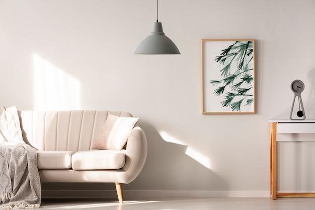 Grijze lamp in lichte woonkamer interieur met poster naast beige bank. echte foto