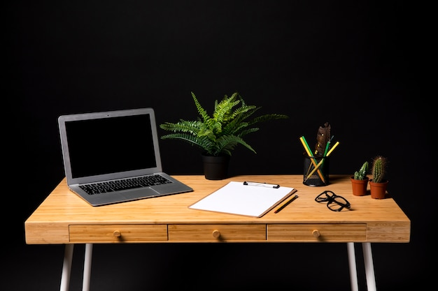 Grijze laptop met klembord en glazen