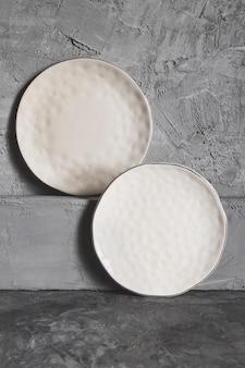Grijze lege platen (keramiek) op een grijze steenachtergrond. grijs minimalisme concept
