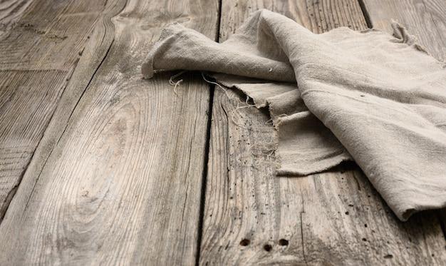 Grijze linnen keukenhanddoek op een tafel gemaakt van oude houten planken, bovenaanzicht, kopie ruimte