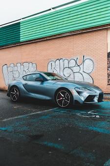 Grijze luxeauto die naast muur met graffiti wordt geparkeerd