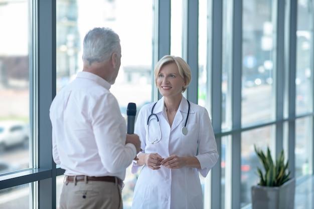 Grijze mannelijke journalist interviewt blonde vrouwelijke arts