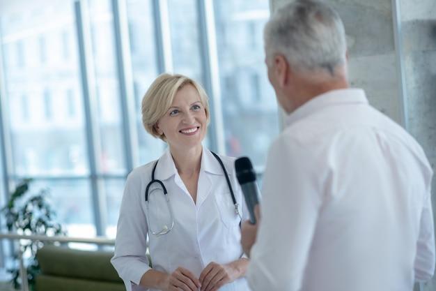 Grijze mannelijke journalist met interview met glimlachende blonde vrouwelijke arts