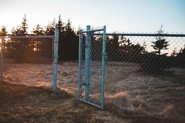 Grijze metalen hek op bruin grasveld overdag