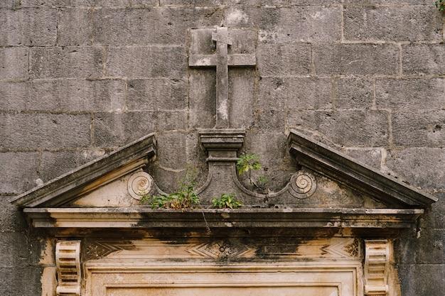 Grijze muur met een kruis uitgehouwen in de steen in de stijl van een bas-reliëf, boven de ingang van de