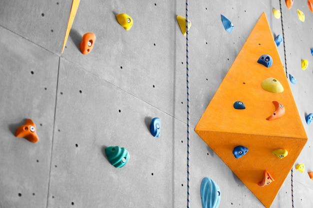 Grijze muur met klimgrepen en touwen in de sportschool