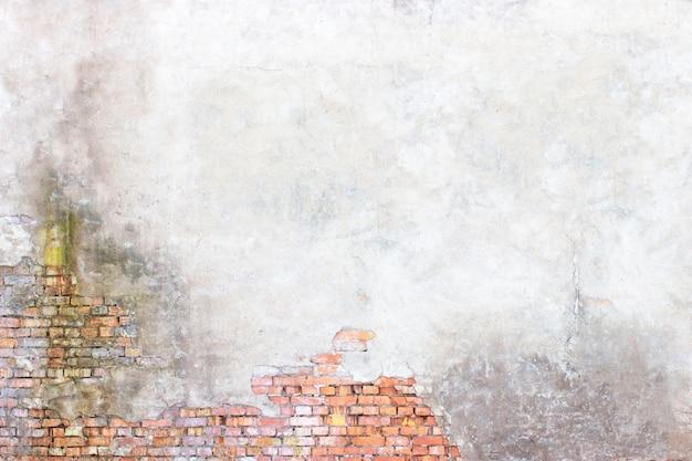 Grijze muur met schil gips en bakstenen