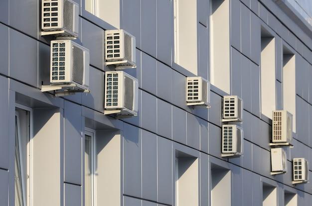 Grijze muur van kantoorgebouw gemaakt van metalen platen met ramen en airconditioners