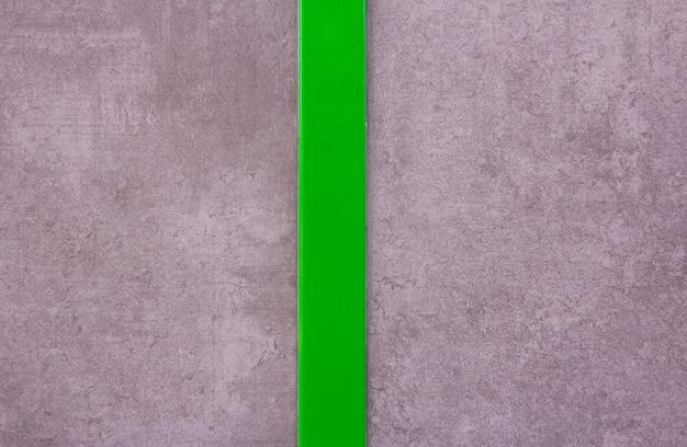 Grijze muurtextuur met gepolijste groene streep in het midden. achtergrond. modern ontwerp.