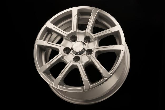 Grijze nieuwe lichtmetalen wiel voor auto, zijaanzicht op zwarte achtergrond.