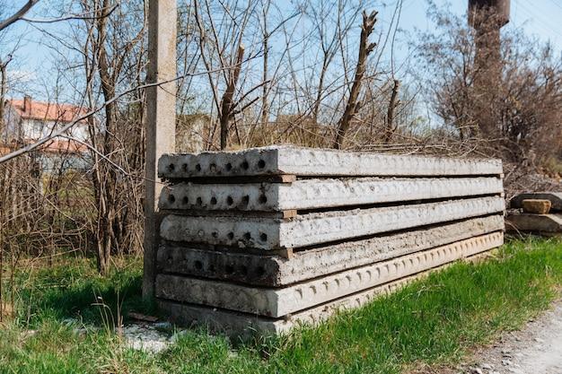 Grijze, oude betonplaten die op een bouwplaats op elkaar zijn gestapeld.