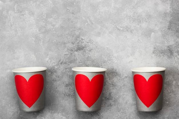 Grijze papieren bekers voor drankjes met rood hart op een lichte achtergrond. bovenaanzicht, kopie ruimte.