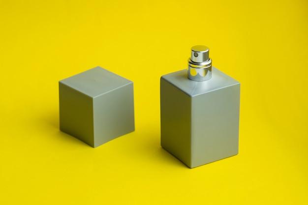Grijze parfumfles op papier achtergrond