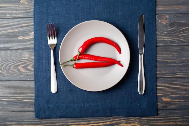 Grijze plaat met chili rode peper op, lepel en mes met blauw linnen tafellaken op tafel