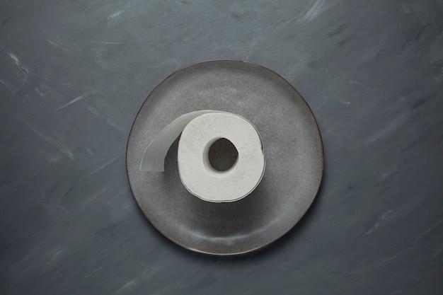 Grijze plaat met een rol wc-papier. close-up, bovenaanzicht.