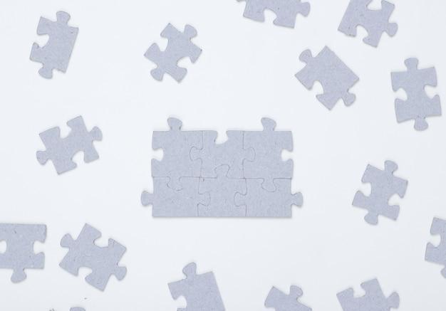 Grijze puzzelstukjes geïsoleerd op wit