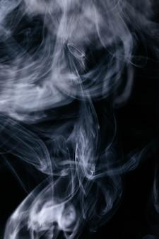 Grijze rookgolven op zwarte achtergrond