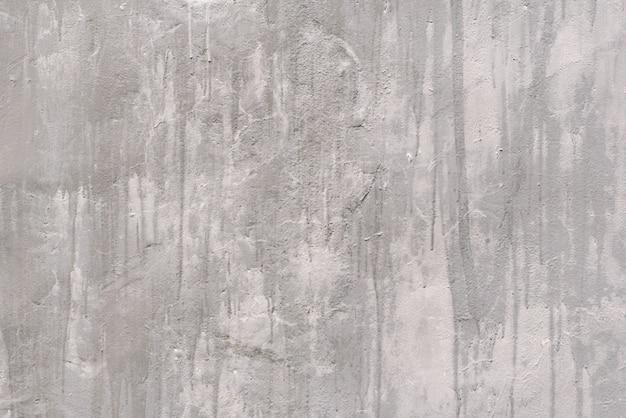 Grijze ruwe gepleisterde muur met vlekken. achtergronden en texturen