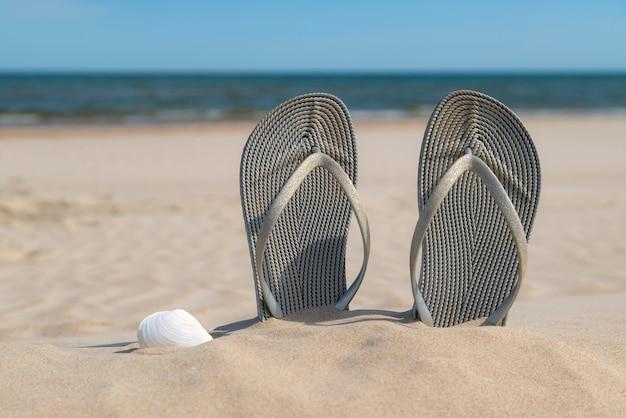 Grijze sandalen op het strand op een mooie zonnige dag.