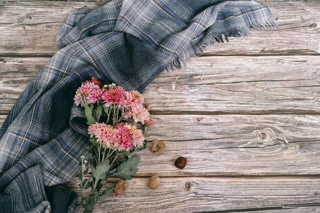 Grijze sjaal en herfstbloemen