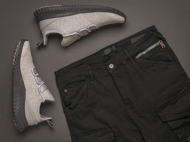 Grijze sneakers en zwarte broek. modieuze vrijetijdskleding voor jongeren.