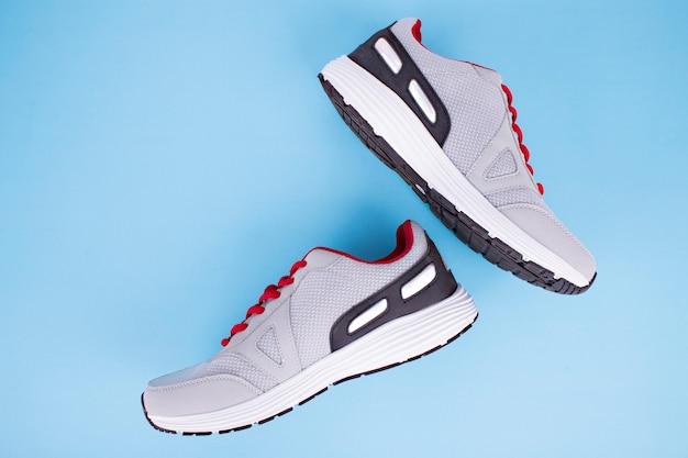 Grijze sneakers met rode veters op blauw