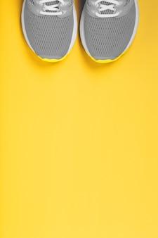 Grijze sneakers op een gele achtergrond met vrije ruimte.