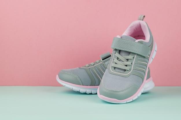 Grijze sneakers voor sport op een tweekleurige achtergrond. sportschoenen.