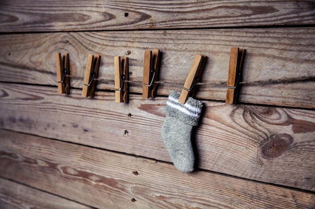 Grijze sok met een wasknijper op een houten en