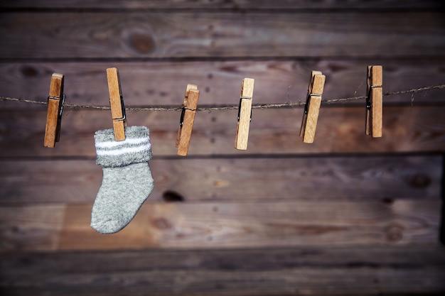 Grijze sok met een wasknijper op een houten muur