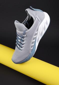 Grijze sportschoenen voor hardlopen met gele buis op donkere ondergrond. concept gezonde levensstijl, sport en fitness. kleur 2021 jaar. modieuze kussen sneakers.