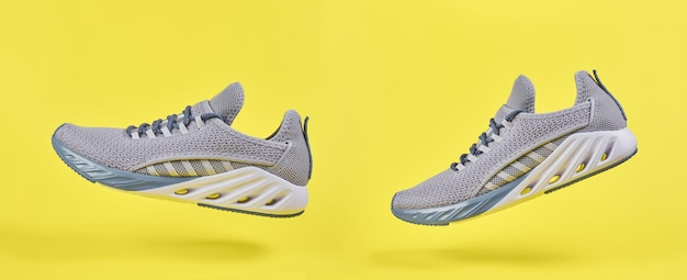 Grijze sportschoenen voor hardlopen op gele muur. concept gezonde levensstijl, sport en fitness. kleur 2021 jaar. modieuze kussen sneakers.