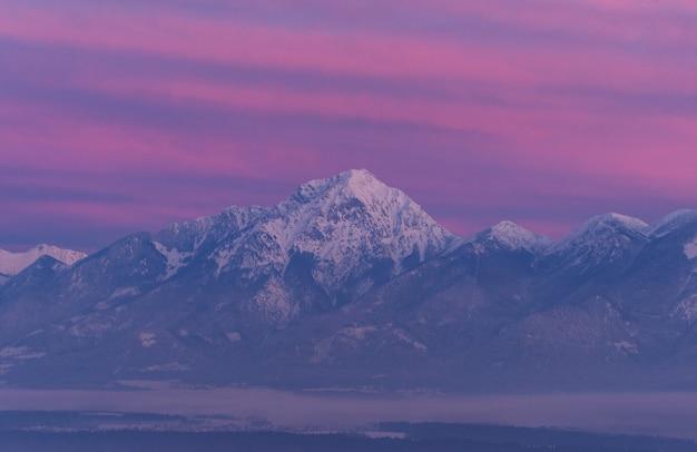 Grijze stenen berg bedekt met sneeuw