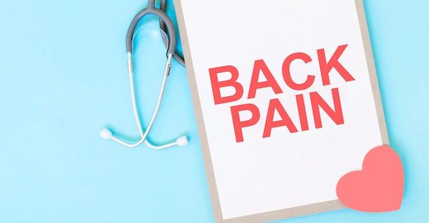 Grijze stethoscoop en papieren bord met een vel wit papier met tekst rugpijn lichtblauwe achtergrond. medisch begrip.