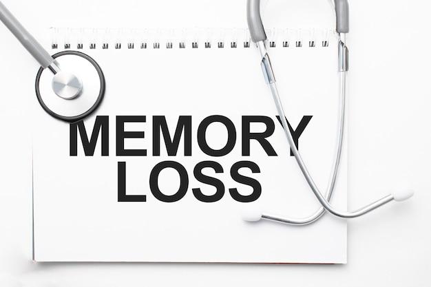 Grijze stethoscoop en papieren bord met een vel wit papier met tekstgeheugenverlies lichtblauwe achtergrond. medisch begrip.