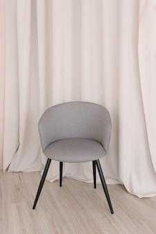 Grijze stijlvolle stoel tegen de achtergrond van de gordijnen in de woonkamer